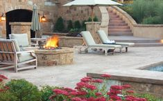 This contemporary patio design is a great place for entertaining, featuring a fire pit area surrounded by lounge chairs and umbrellas, accented by bright flowers. Fire Pit Area, Fire Pit Backyard, Backyard Patio, Outdoor Kitchen Design, Patio Design, Ensemble Patio, Fire Pit Decor, Fire Pit Lighting, Stair Lighting