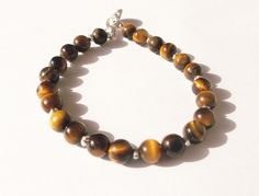 Brown tigers eye gemstone beaded bracelet. Golden brown, polished tigers eye stone accented with delicate silver plated spacer beads create this beautiful bracelet.