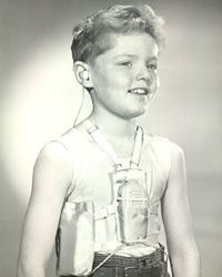 Boy model wearing body aid hearing device and underarm battery harness abt 1930-40