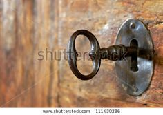 Closeup of an old keyhole with key on a wooden antique door - stock photo