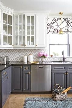 Stunning kitchen features white upper cabinets and gray lower cabinets adorned with brass hardware paired with black quartz countertops and white and gray marble chevron backsplash tiles. by adrian