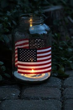 Stick two flags to an old jar using spray adhesive, then use Mod Podge to seal. Put a small amount of sand in the bottom of your jar and add a votive candle. Make one or several to line your sidewalk.