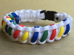 Autism Awareness Paracord Bracelet - White cobra stitch paracord bracelet with Red, Blue, Green and Yellow Accent using Fid/Needle #TritonParacord #ParacordBracelet #AutismAwareness