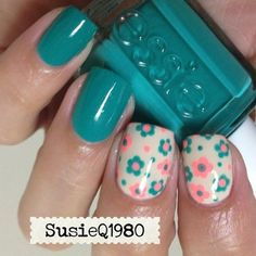 Teal manicure with teal and coral pink flowers on cream accent nails