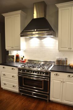 """the Bertazzoni Heritage 36"""" gas range, with the hood in matte black, to match the cabinetry on the island. The kitchen backsplash is made up of white 3"""" x 6"""" subway tile with gray grout from a local tile store."""