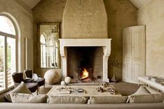 Mansion in Belgium with barn converted into a living room with a large fireplace with molded mantel, taupe sofa, light wood coffee table, two wingback chairs, a large traditional mirror and light wood cabinet