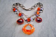 A healthy dose of vibrant orange and purple recycled art glass discs, sea glass nuggets, and glass teardrops dance along two copper chains. The discs are recycled art glass that has been flame-worked and hand sculpted. Copper lobster clasp.