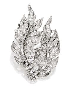 A PLATINUM AND DIAMOND DOUBLE FEATHER BROOCH, VERDURA,  1956   designed as curved feathers, set with two old mine-cut diamonds together weighing approximately 2.45 carats, further enhanced by numerous old mine, single, and baguette-cut diamonds, weighing approximately 15.50 carats, unsigned; may be worn as two clips.