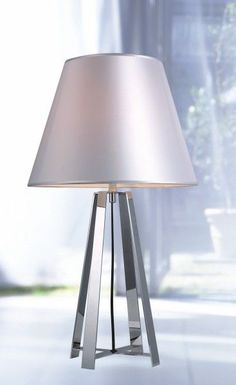 """Modrest KM064T Modern Stainless Steel Table Lamp. The Modrest KM064T modern stainless steel table lamp features an elegant design with a silken fabric shade. A sturdy stainless steel base provides able support. It requires 1 E27 bulb and measures W14"""" x D14"""" x H24"""". Dimensions: W14"""" x D14"""" x H24"""" Color: Other Finish:   -"""