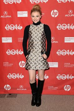 Chloe Grace Moretz layered a sleeveless tunic mini-dress from the Christopher Kane spring 2014 collection over a black turtleneck. This look is such an easy way to wear your off-season pieces right now. Chloe went with knee-high boots and bare legs, but you could throw on a pair of tights for extra warmth.