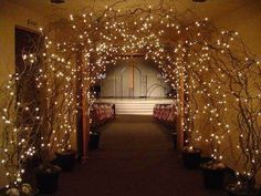 Beautiful lighted twig archway, love it. It is outdoor wedding but there has to be nearby building with restrooms, etc. This would be decor. Plus candles and flower petals on floor. -Mari