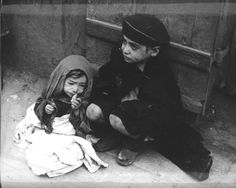 Warsaw, Poland, Two starving children on the pavement in the ghetto.
