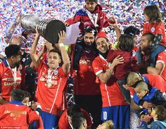 Alexis Sanchez gets his hands on the hefty Copa America trophy as members of the team are joined by their family in celebrating. 4.7.15