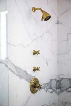 Dana Benson Construction - Statuary marble walk in shower is equipped with a vintage brass cross handle shower kit.