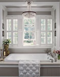 In this luxurious master bath, the whirlpool tub, set below oversize windows and highlighted by a crystal chandelier ($300 on eBay!), is the star. Interior shutters lend privacy while filtering sunlight. Framed back-and-white silhouettes call attention to the crisp grid created by the wood-paneled walls. For more of this beautiful bathroom, check out our web-exclusive detail shots and shopping guide.