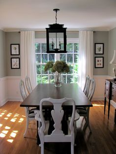 also love the simplicity of the room the paint color the art framing the windowand the dark table with white chairs