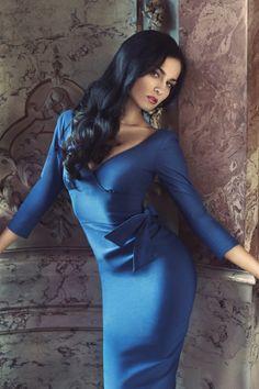 Nina de Lianin in a blue dress, with long wavy black hair
