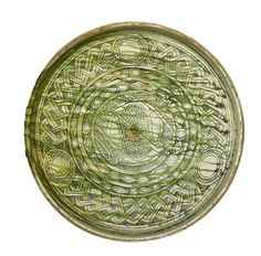 A large splashed and incised pottery dish, Persia or Central Asia, 11th/12th century of shallow rounded form with tall, slightly everted rim, with a cream slip ground incised with stylised facing birds in the centre surrounded by bands with geometric motifs and twisted cord design, with green and brown splashed glazes 39.7cm. diam.