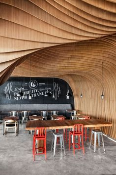 "Undulating layers of timber create a cave-like interior inside this ""6 Degrees Cafe"" in Indonesia by local studio OOZN Design"