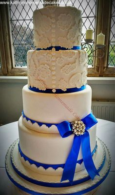 4 tier wedding cake, with lace detail and bow
