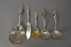 """Reed & Barton """"Love Disarmed"""" five sterling silver pieces to include pea/cracker server lg. 8 3/4 in., two gravy ladles lg. 6 1/2 in., master buttler knife lg. 7 1/2 in., and preserve spoon lg. 6 in. with gold washed bowl."""