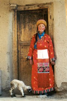 Asia | Portrait of a young Tibetan woman wearing traditional clothes and hat, standing outside with her lamb, Tibet