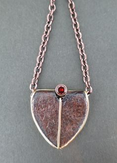 """A 2016 """"Unbreakable Heart"""", """"Heart Divided with Red"""", made of 18k yellow gold, sterling silver and rusted iron with bezel-set 5mm garnet on a brown stainless steel chain with 18k rose gold clasp and catch. Designed and made by llyn strong."""