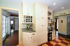 White cabinets and a built-in desk in a kitchen. The floors are heated. There is also a wine rack built into the kitchen cabinets.