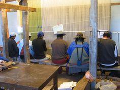 Craftswomen and craftsmen weaving a carpet