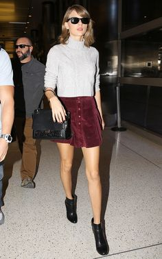 Taylor Swift wears a cropped cable knit sweater, corduroy miniskirt, top-handle bag, Ray-Ban sunglasses, and black heeled ankle boots