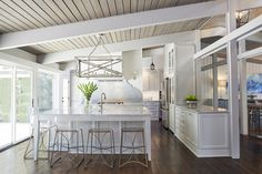 Traditional kitchen inspiration, with white cabinetry on dark timber floors - Found on ELLEDecor.com