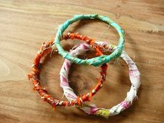 fabric bangles: use an old guitar string, trim ends with wire cutter, shape into circle, wrap in place with electrical tape, cut strip of desired fabric, wrap strip of fabric around electric tape wrapped guitar string, tie off end of fabric.