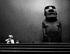 An elderly woman sits reading by a large stone statue, or moai from Easter Island on display at the British Museum, London, (Photo by Romano Cagnoni/Hulton Archive/Getty Images) British Museum, Photografy Art, Royal Navy Frigates, Easter Island Statues, Happy Eyes, Emotional Photography, Stone Statues, Great Photographers, Color Photography