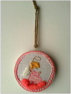 Angelito bordado a mano sobre lino. Lana e hilo de algodón.