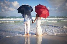 Trouwfoto op het strand met rode en paarse paraplu.