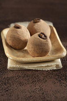 1 lata de Leite MOÇA® Tradicional  - 1 colher (sopa) de NESCAFÉ® Original  - 1 colher (sopa) de manteiga  - 1 xícara (chá) de nozes moídas  - 1 xícara (chá) de Chocolate em Pó DOIS FRADES®  - 1 colher (sopa) de manteiga para untar  - 40 grãos de café para decorar  -
