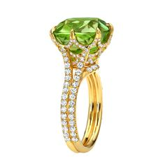 "Tamir Exceptional Peridot And Diamond Web Ring. A web of 1.18ct single-cut diamonds provides a setting for this magnificent and ""electric"" 11.46ct cushion Peridot, with two rows of diamonds down the shank. Signed by Tamir, c 2013"