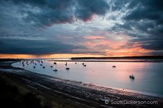 Commercial salmon fishing boats rest at anchor in the Naknek River under a dramatic Bristol Bay sunset, Alaska.