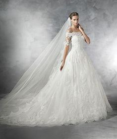 Pleasant by Pronovias Princess-style tulle wedding dress. Off-the-shoulder bodice and elbow-length sheer sleeves with lace appliqués. Round neckline and sheer back adorned with appliqués. Tulle and la