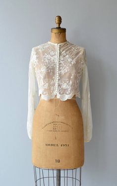 Vintage 1950s ivory lace jacket/blouse with high neckline, lace buttons, long sleeves and scallop hem. --- M E A S U R E M E N T S --- fits like: small shoulder: 15 bust: 38 sleeve: 23 length: 15 brand/maker: n/a condition: excellent ➸ More tops & sweaters https://www.etsy.com/shop/DearGoldenVintage?section_id=5800171 ➸ Visit the shop http://www.DearGolden.etsy.com _____________________ ➸ instagram | deargolden ➸ twitter | deargolden ...