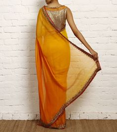 I am in love with this shade of Yellow Ochre and dull Orange Chiffon Saree. You can either go with the silver or gold lame blouse or do something else.