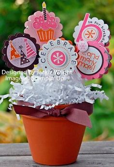 party table centrepiece with cake topper discs, shredded paper and a pot/bucket