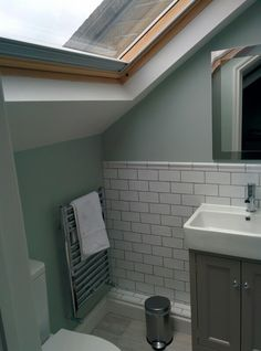 Small loft conversion bathroom shower room in SE London Wall paint - Little green salix Floor tiles - Rye Harbour limed, Fired Earth Wall tiles - chico blanco tiles, Tops Tiles. Skirting and ceiling - Slaked Lime, little green Mirror - John Lewis Vanity unit - Roper Rhodes