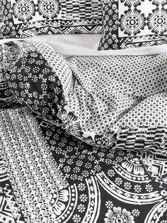 Tyla Quilt Cover Set. Tyla's lively patchwork of black and white folk motifs and patterns is printed on a soft cotton slub, bringing a natural, textural aesthetic to the bedroom. Finished with black cord piping and a simple, printed reverse.