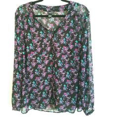 Torrid Plus Size 1X Black Floral Print Chiffon Top This Torrid Plus Size 1X Black Floral Print Chiffon Top is in great used condition. Buttons up with fabric covered buttons. 2 pockets on front.  Pretty floral print including pink, violet, and blue in 100% polyester, no stretch. Bust measures 23 inches across laying flat, measured from pit to pit, so 46 inches around. 28.5 inches long. ::: Bundle 3+ items from my closet and save 30% off when you use the app's Bundle feature! ::: No trades…