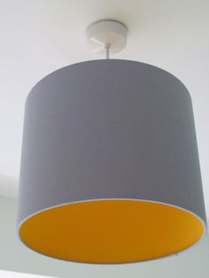 Handmade fabric drum lampshade in Light Grey with a colour of your choice fabric interior lining for a real contemporary look.  Colours available: Orange or Sunshine Yellow (other colours available Turquoise, Hot Pink, Bright Red)  This beautiful shade can be used with a lamp base or with a ceiling pendant. The shade glows with a tint of the lining colour.   Sizes available: 20 cm wide x 20 cm high, 25 cm wide x 23 cm high, 30 cm wide x 24 cm high, 35 cm wide x 24 cm high and 40 cm wide x 25…