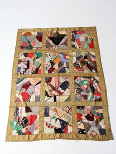 "circa 1900sBeautifully aged, this is an antique crazy quilt blanket. The patchwork quilt features multiple textiles with a gold satin border. There is an embroidered heart at the top. The backing is a soft gray cotton.  multiple textile patchwork blanket ""Crazy"" quilt pattern gold tone satin ""frame"" between the multiple textile patchwork embroidered heart at top gray tone cotton blend backing  CONDITIONThe quilt is aged with some patches fraying.  MEASUREMENTS    Length 76.5 inch    Width…"