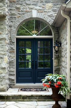 Double front entry door in a deep blue perfectly plays off the pale grey rock siding.