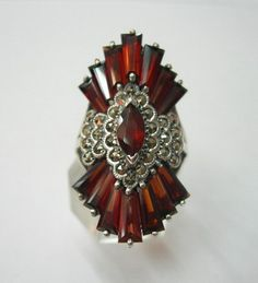 A beautiful deep red African Garnet surrouded with Marcasite stones set in a 92.5 % silver ring.
