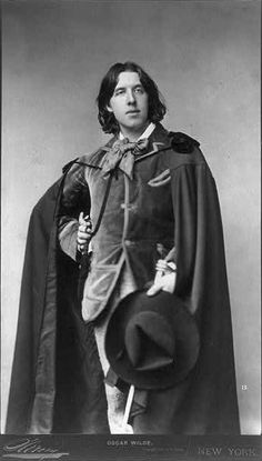 Napoleon Sarony portrait of Oscar Wilde standing in cape with hat in hand (1882)